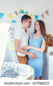 Happy young expecting couple in love standing near a new baby crib