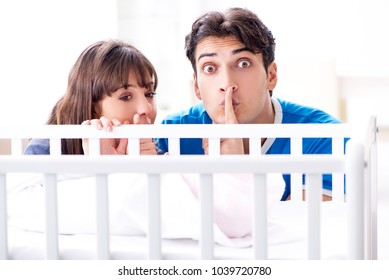 Happy young family at baby bed cot
