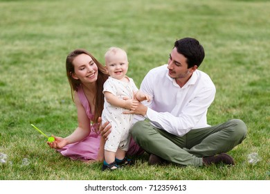 Happy young family with baby boy spending time together outside in green nature at summer