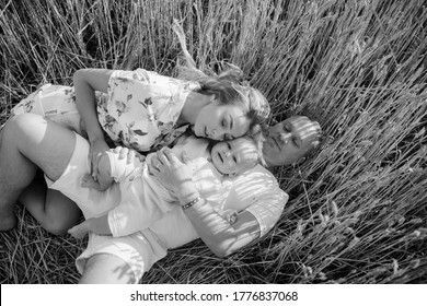 Happy young family with baby lying and resting among yellow wheat field. Closeup. Black and white image.