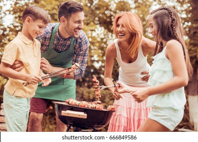Happy young family barbecuing meat on the grill.