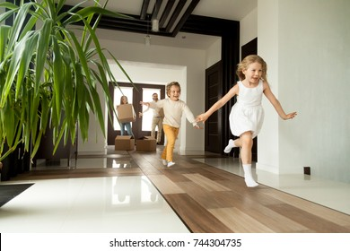 Happy young family with cardboard boxes in new home at moving day concept, excited children running into big modern own house hallway, parents with belongings at background, mortgage loan, relocation