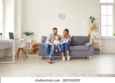 Happy young family with child sitting on comfy soft gray couch in spacious studio apartment or living-room of new house, reading book together, enjoying quiet leisure time on weekend at home