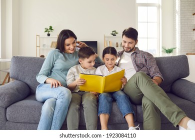Happy young family with children enjoying free time resting on couch at home. Parents and kids sitting on soft comfy sofa, reading book of fairy tales or looking through holiday photo album together