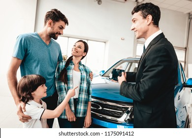 Happy Young Family Are Choosing A New Car In Showroom. Dialogue With Dealer. Cheerful Customer. Automobile Salon. Make A Decision. Information On Tablet. Good Offer. Buyer And Seller. Business Trade.