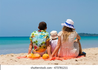 Happy young family with coconut on a tropical beach