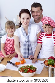 Happy young family cutting vegetables in kitchen