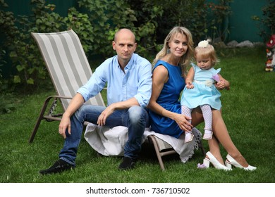 Happy young family. Dad, mom and little beautiful daughter. Young couple sitting on a deckchair.