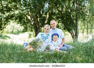 Happy young family with daughter spending time together outside in green nature.