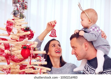 happy young family decorate decorate eco christmas tree at home
