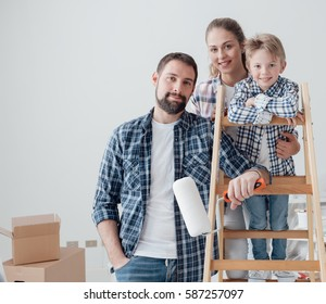 Happy young family doing a home makeover, they are posing together, the man is holding a paint roller and the woman is holding her son on a ladder