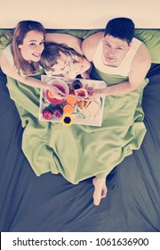 happy young family eat breakfast in bed at morning