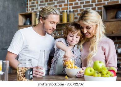 happy young family eating corn flakes for breakfast at home