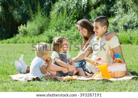 Happy young family of four having picnic at meadow at summer day