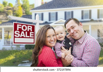 Happy Young Family In Front of For Sale Real Estate Sign and House.