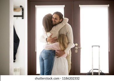 Happy young family in hallway near entrance door at home. Husband hugging wife and little preschool daughter with tenderness and love, with suitcase luggage arrived from business trip, reunion concept