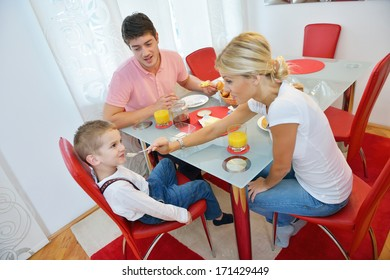 happy young family have healthy breakfast at kitchen with red details on bright morning light