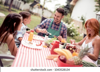 Happy young family having barbecue lunch in the garden on a sunny day.
