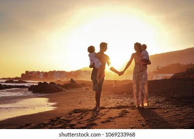 Happy young family having fun walking on beach at sunset