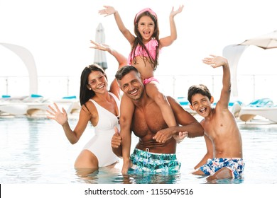 Happy young family having fun inside a swimming pool outdoors in summer, waving hands