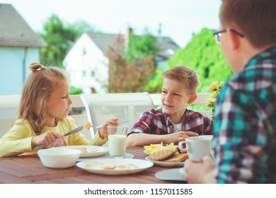 Happy young family having fun during breakfast on the big terrasse at home