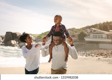 Happy young family having fun on beach vacation. Father carrying his son on shoulders with mother supporting the boy.