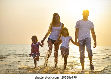 Happy young family having fun running on beach at sunset. Toned photo. Family traveling concept. No effects - real sun