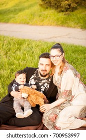 Happy young family with her son in a walk in the park. Family spending quality time together