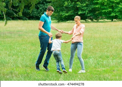 Happy Young Family Holding Each Other Hands While Playing In The Park