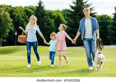 happy young family holding hands while walking with pet in park