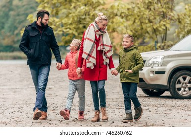 happy young family holding hands while walking together in autumn park