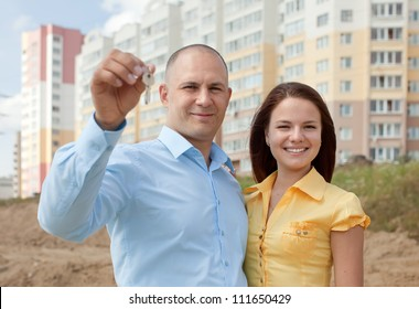 happy young family with key  in front of new home