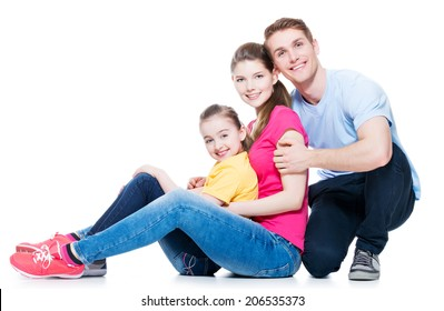 Happy young family with kid sitting on the floor at studio - isolated on white.