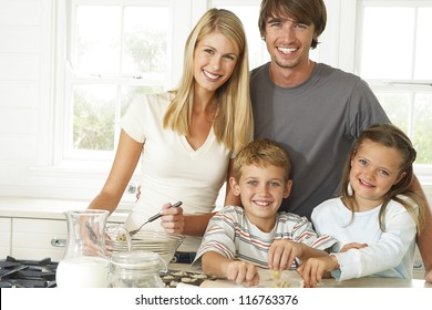 Happy young family in the kitchen with Mum, Dad and their young son and daughter posing together while baking cookies