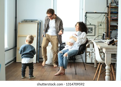 Happy young family laughing and dancing at homу