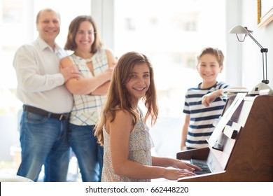 Happy young family listening how children plays piano music at home
