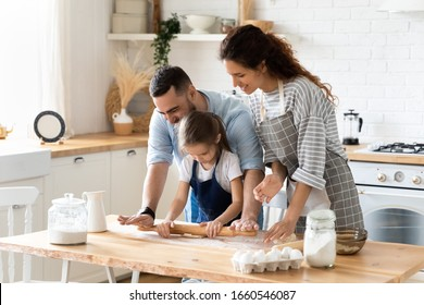 Happy young family with little daughter have fun making dough preparing baking cookies or pastries together, excited parents teach small preschooler girl child doing bakery cooking pie together