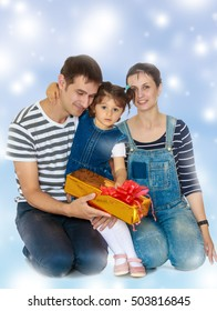 Happy young family with little daughter cuddling together in celebration of Christmas.Blue Christmas festive background with white snowflakes.