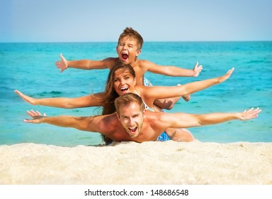 Happy Young Family with Little Kid Having Fun at the Beach. Joyful Family. Travel and Vacation