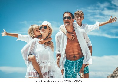 Happy young family with little kids having fun at the beach. Mom and dad piggyback their sons.