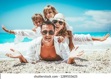 Happy young family with little kids having fun at the beach.