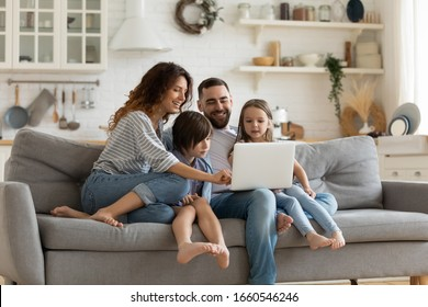 Happy young family with little kids sit on sofa in kitchen have fun using modern laptop together, smiling parents rest on couch enjoy weekend with small children laugh watch video on computer at home - Shutterstock ID 1660546246