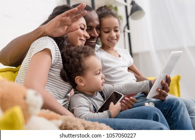 happy young family making video call with tablet at home