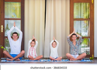 Happy young family meditating on the terrace