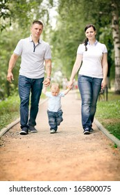 happy young family mom dad and baby in the park