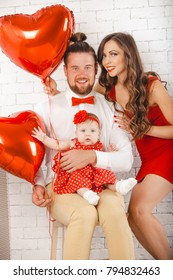 Happy young family mother, father and daughter posing in studio.