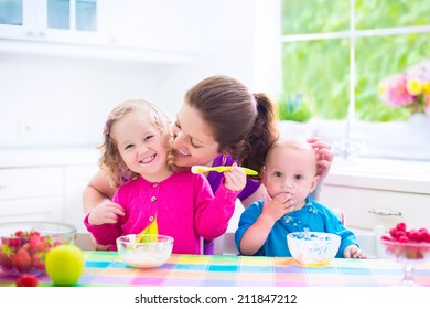 Happy young family, mother with two children, adorable toddler girl and funny messy baby boy having healthy breakfast eating fruit and dairy, sitting in a white sunny kitchen with window