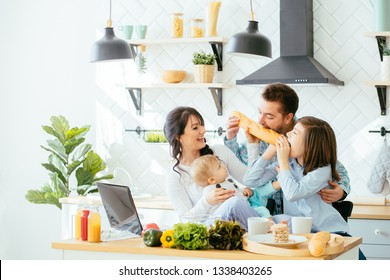 Happy young family with Mum, Dad and two different age children cooking breakfast, laughing biting the baguette in the kitchen preparing meal together.