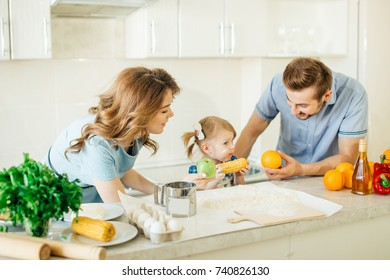 Happy young family with Mum, Dad and two young children cooking in the kitchen