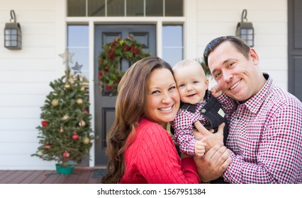 Happy Young Family On Front Porch of House With Christmas Decorations.
